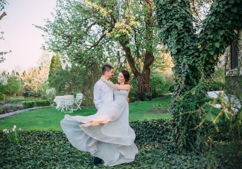 El marido está circundando a su mujer preferida en los brazos Muchacha pelirroja en un vestido modesto, gris en estilo rústico st fotos de archivo