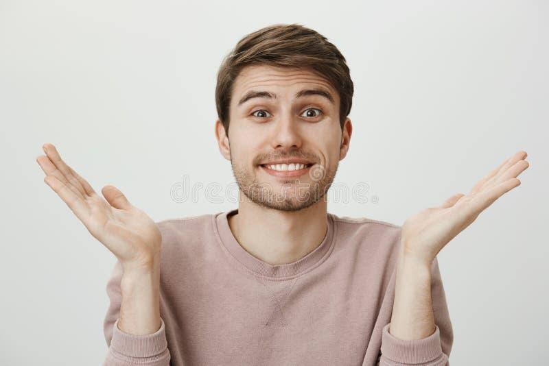 El marido no tiene ninguna idea Retrato interior del hombre joven hermoso con la cerda que encoge y que aumenta las palmas, sonri fotos de archivo libres de regalías