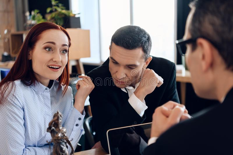 El marido trastornado se está sentando con la esposa joven detrás de la tabla del ` s del abogado de divorcio imagen de archivo