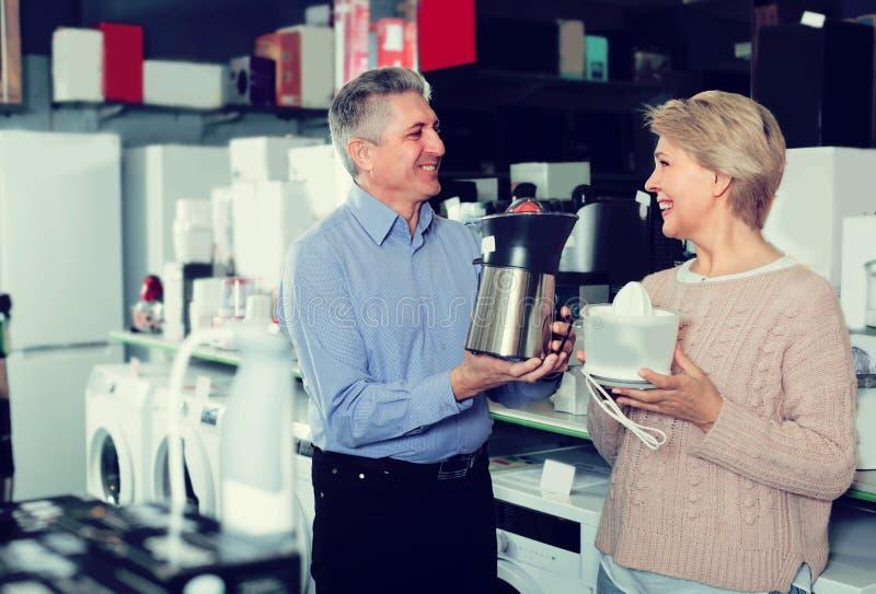 El marido y la esposa están comprando en la tienda de los aparatos electrodomésticos juic fotos de archivo libres de regalías