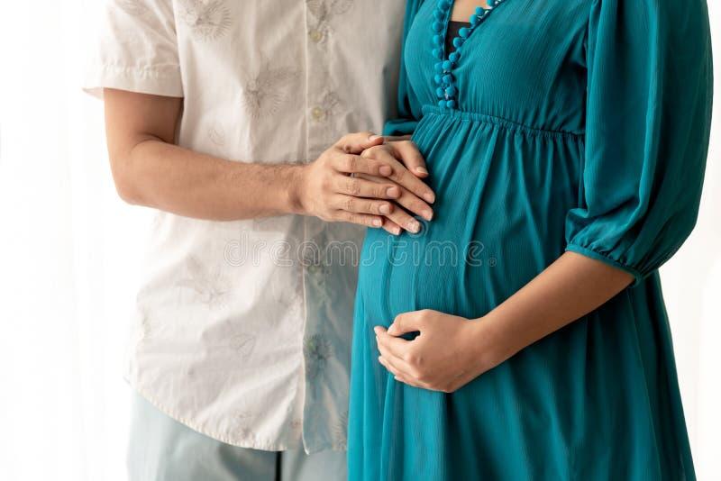 El marido y la esposa utilizan sus manos para apoyar su estómago fotografía de archivo libre de regalías