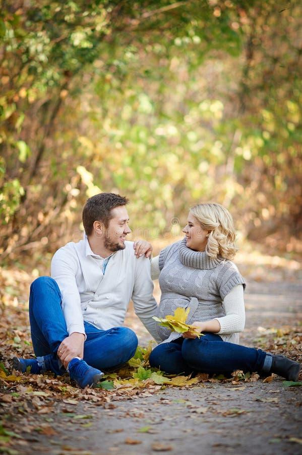 El marido y su esposa embarazada que se relajan en otoño parquean fotos de archivo libres de regalías
