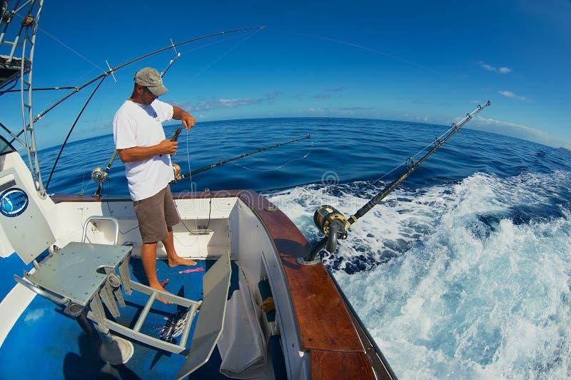 El marinero consigue carretes y las barras listos para la pesca de juego de la aguja en el mar cerca de Saint Denis, Reunion Isla fotografía de archivo