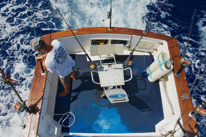 El marinero consigue carretes y las barras listos para la pesca de juego en el mar cerca de St Denis, Reunion Island fotografía de archivo