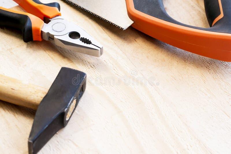 El martillo, los clavos y los alicates mienten en un fondo de madera La construcción equipa el foco selectivo fotos de archivo libres de regalías