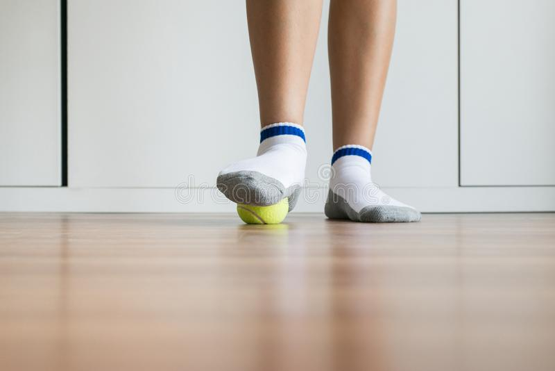 El masaje de la mujer con la pelota de tenis a su pie en el dormitorio, pies de masaje de los lenguados para el fasciitis plantar fotos de archivo