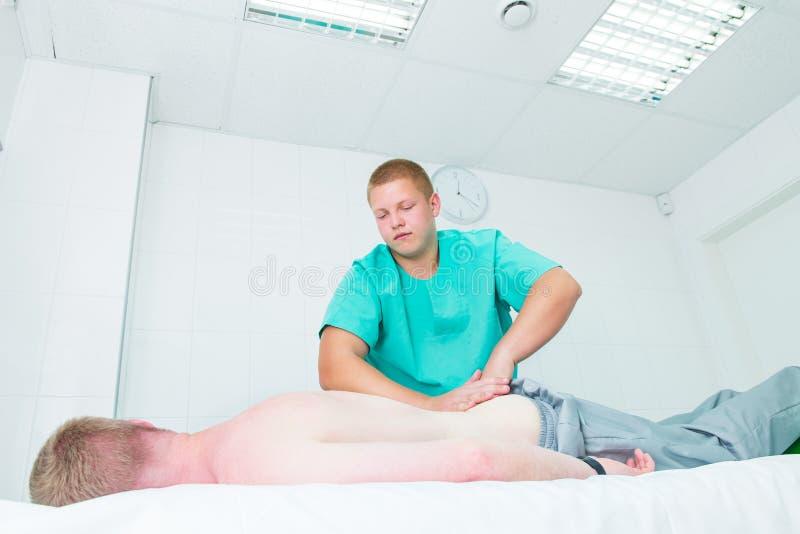 El masaje de recepción paciente del quiropráctico del terapeuta A hace masaje profundo del tejido en los lomos del hombre en ofic fotos de archivo libres de regalías