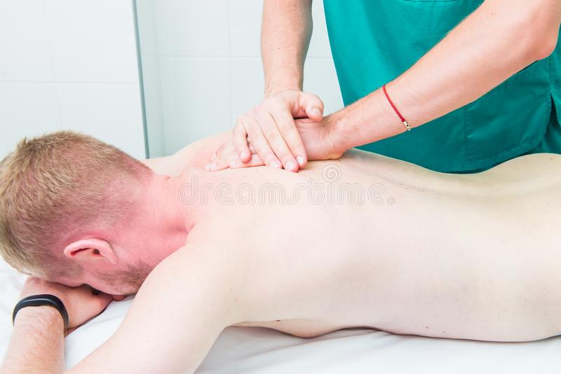 El masaje de recepci?n paciente del quiropr?ctico del terapeuta A hace masaje profundo del tejido en el om?plato del hombre en of imagenes de archivo