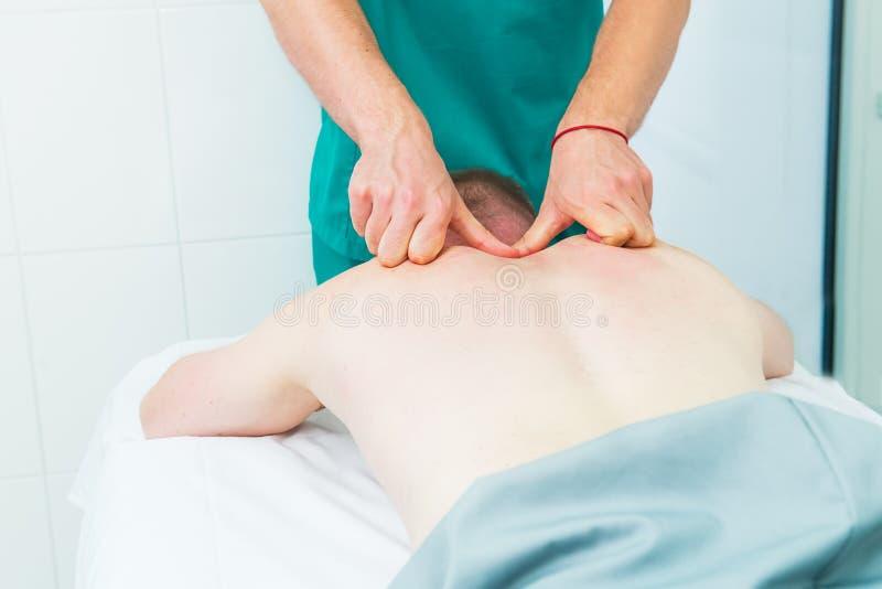 El masaje de recepci?n paciente del quiropr?ctico del terapeuta A hace masaje profundo del tejido en el om?plato del hombre en of fotografía de archivo