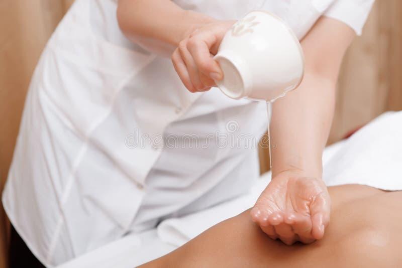 El masajista da masajes a una mujer foto de archivo libre de regalías