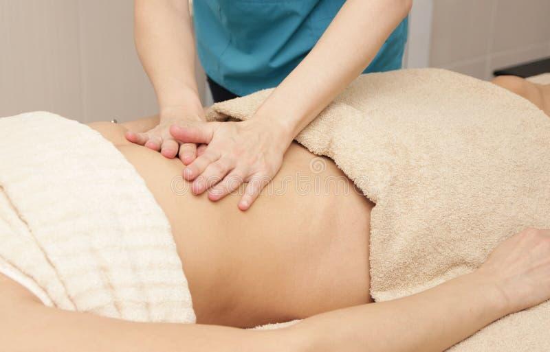El masajista hace el masaje de la cura del abdomen para una mujer foto de archivo