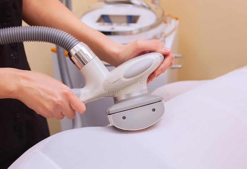 El masajista hace un masaje del hardware en el asno y las piernas pacientes en un traje blanco, primer del ` s imagen de archivo