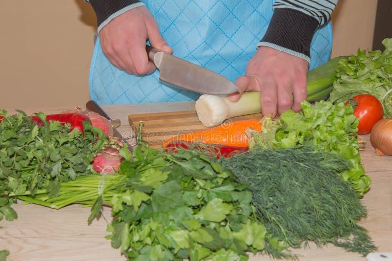 El ` masculino s da cocinar la comida sana en la cocina, detrás de verduras frescas Alimento sano Imagen cosechada de las verdura foto de archivo
