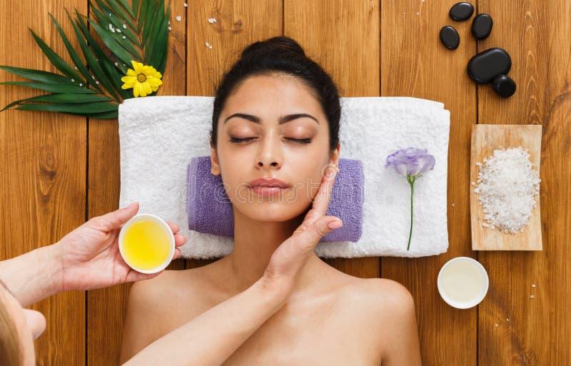 El massagist de la mujer hace masaje de la elevación de cara en centro de la salud del balneario foto de archivo libre de regalías