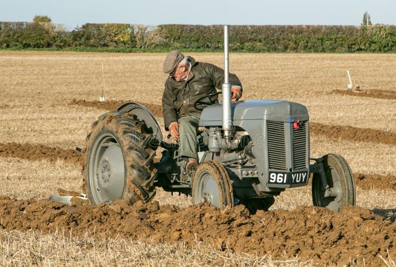 El massey gris viejo fergusen el tractor en el partido de arado fotografía de archivo