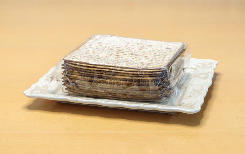 El matzo del embalaje para la forma del cuadrado de Pesach envuelto en un paquete del celofán miente en una placa en la tabla imágenes de archivo libres de regalías