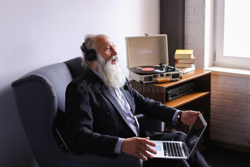 El mayor trabaja en el ordenador y disfruta de música en los auriculares a través imagenes de archivo