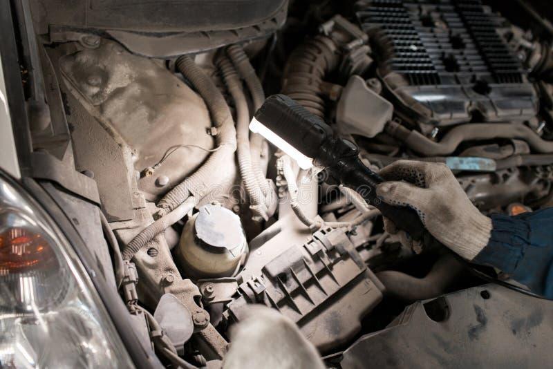 El mecánico da controlar de la utilidad del coche en capilla abierta, cierre para arriba imagen de archivo libre de regalías