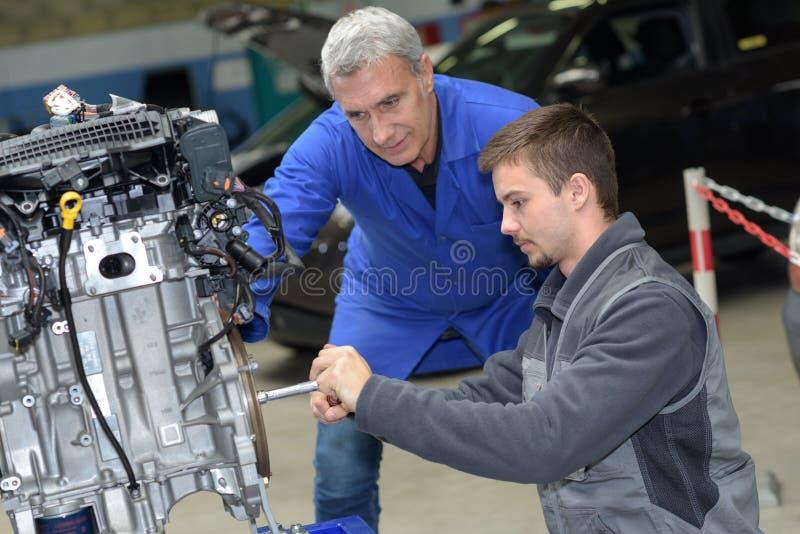 El mecánico de automóviles muestra el motor de coche del mantenimiento del aprendiz fotografía de archivo libre de regalías