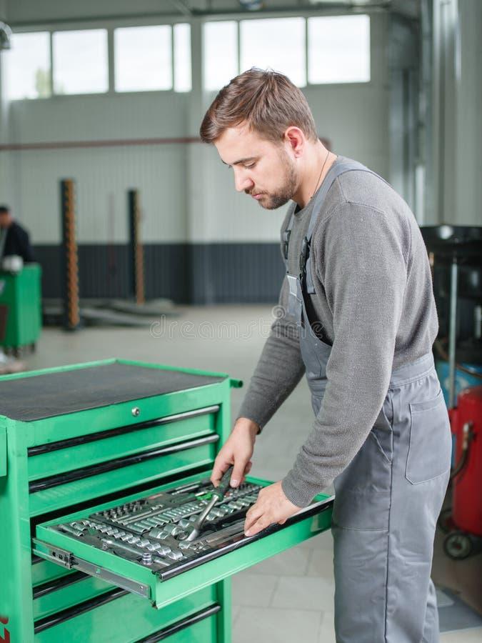 El mecánico de automóviles toma la herramienta de la caja de herramientas dentro imagen de archivo