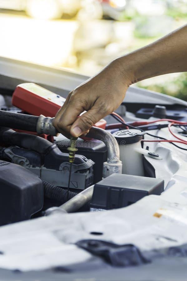 El mecánico de automóviles utiliza la mano del motor de comprobación o de fijación del técnico foto de archivo libre de regalías