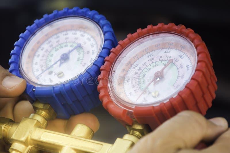El mecánico de automóviles utiliza un indicador de presión en el compresor de aire, líquido imágenes de archivo libres de regalías