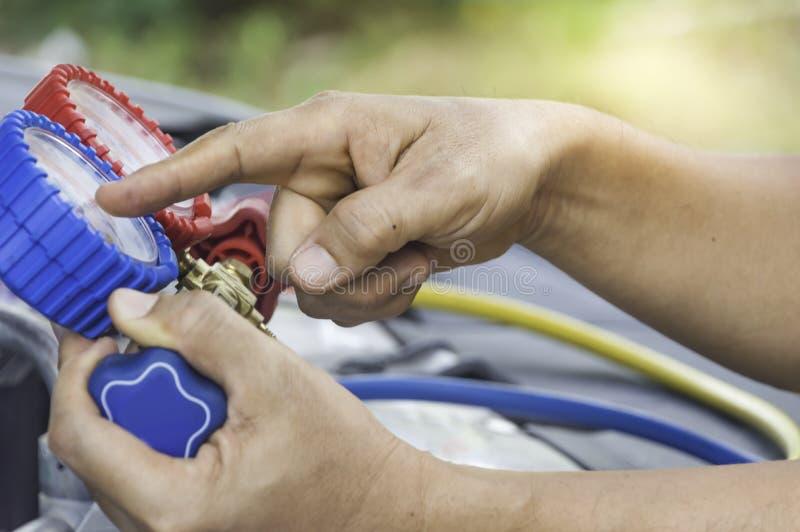 El mecánico de automóviles utiliza un indicador de presión en el compresor de aire, líquido imagenes de archivo