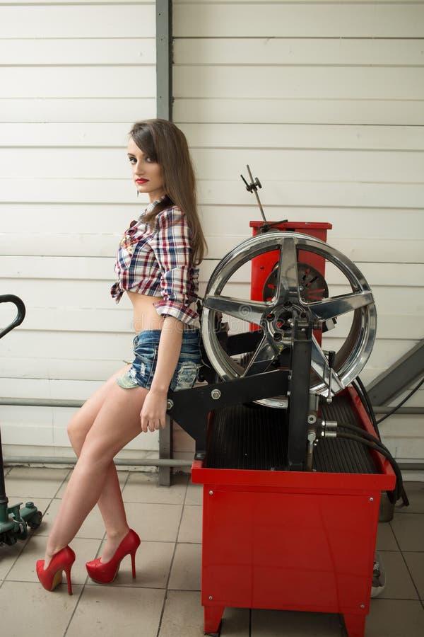 El mecánico de la muchacha substituye los neumáticos en las ruedas imagenes de archivo