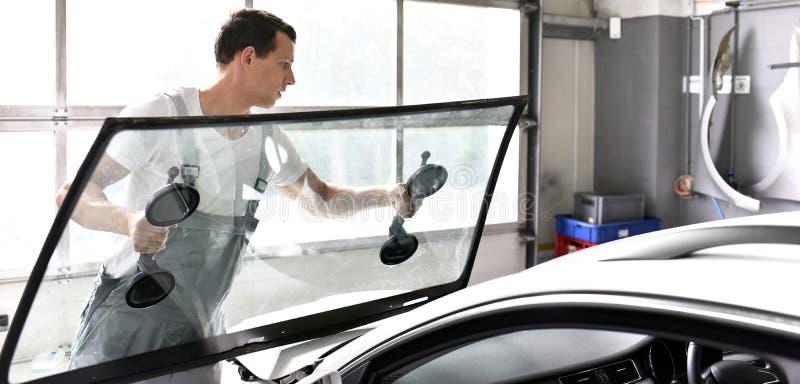 El mecánico en un garaje substituye el parabrisas defectuoso de un coche imagenes de archivo