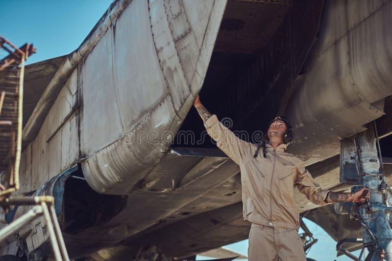 El mecánico en uniforme realiza mantenimiento de un combatiente-interceptor de la guerra en un museo al aire libre imagen de archivo libre de regalías
