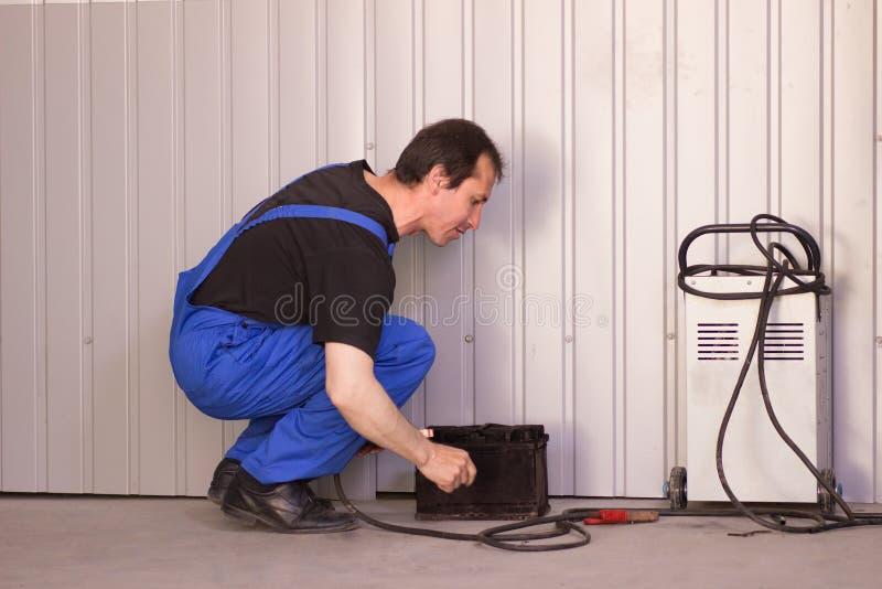 El mecánico está bombeando para arriba rueda en la gasolinera foto de archivo
