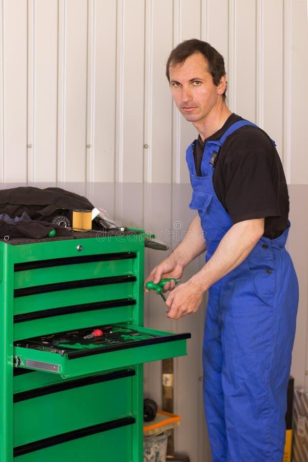 El mecánico está bombeando para arriba rueda en la gasolinera fotografía de archivo libre de regalías