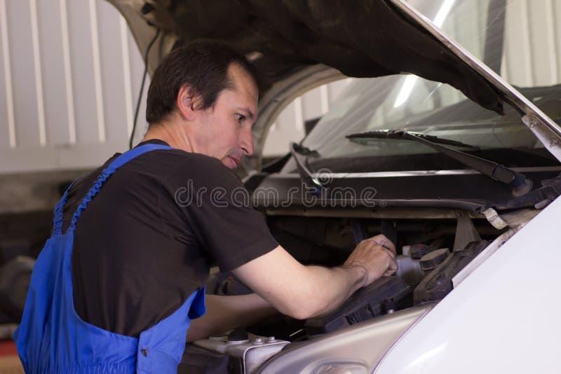 El mecánico está bombeando para arriba rueda en la gasolinera imagenes de archivo