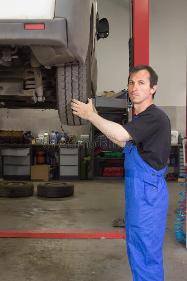 El mecánico está bombeando para arriba rueda en la gasolinera imagen de archivo