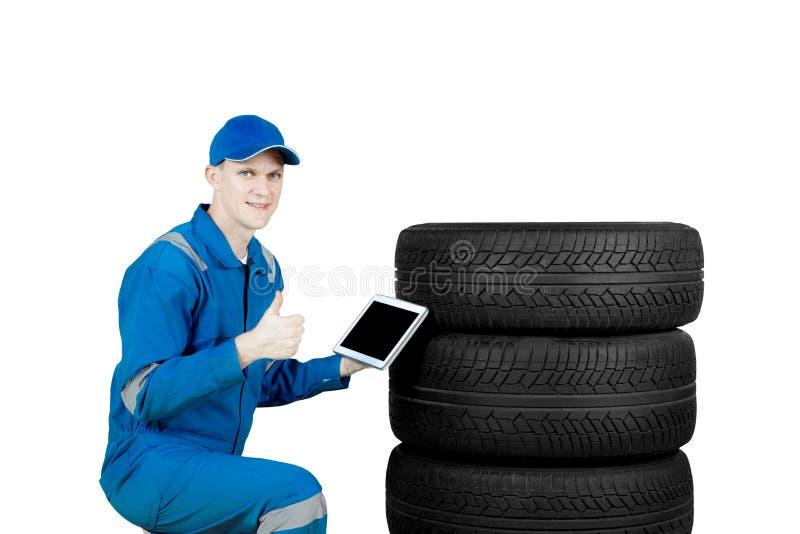 El mecánico europeo muestra el pulgar encima de los neumáticos cercanos fotos de archivo