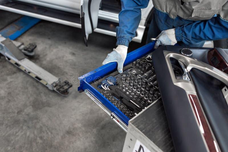 El mecánico selecciona la herramienta Herramientas para la gasolinera llaves inglesas y bocas del zócalo imagen de archivo