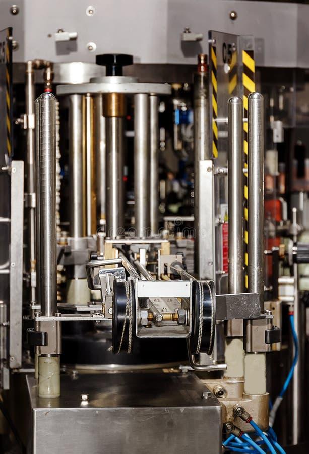El mecanismo de la máquina que capsula de la botella automática Fábrica para la producción de bebidas alcohólicas fotografía de archivo