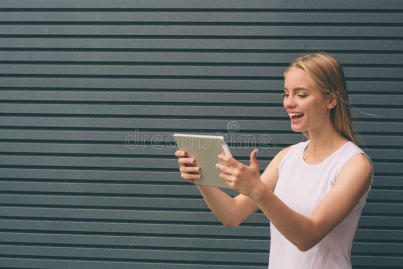 El mecanografiar femenino en la pantalla táctil de la tableta digital al aire libre, de la muchacha del inconformista que usa la  imagenes de archivo