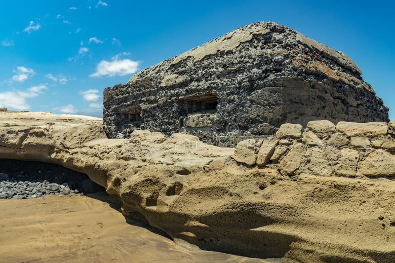 El Medano南海岸的看法  与耸立在海滨的两发射孔的老军事地堡 明亮的天空蔚蓝, 免版税图库摄影
