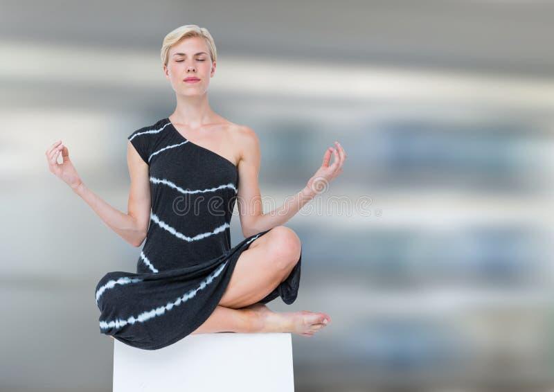 El meditar de la mujer pacífico contra fondo de la falta de definición de movimiento imágenes de archivo libres de regalías