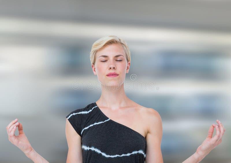 El meditar de la mujer pacífico contra fondo de la falta de definición de movimiento foto de archivo