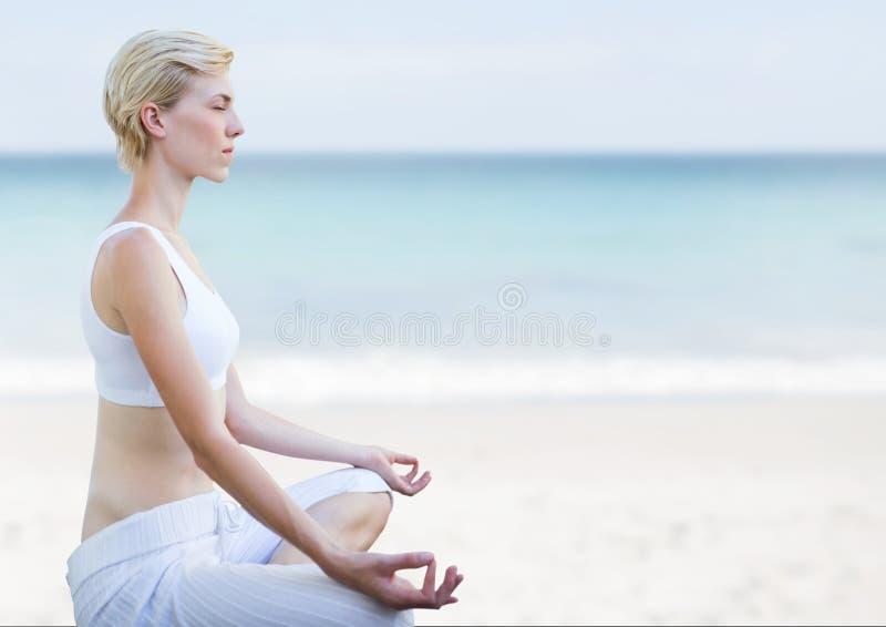 El meditar de la mujer pacífico en la playa fotografía de archivo libre de regalías