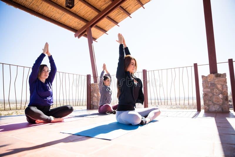 El meditar en actitud fácil de la yoga en la clase fotos de archivo