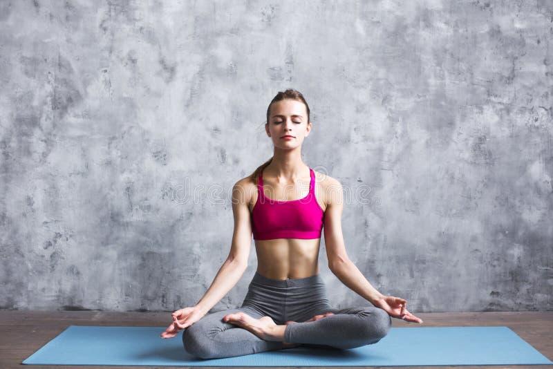 El meditar femenino apto en actitud del loto en casa mujer que hace ejercicio de la yoga dentro imagen de archivo