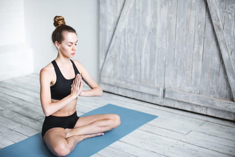 El meditar femenino apto en actitud del loto en casa mujer que hace ejercicio de la yoga dentro fotos de archivo