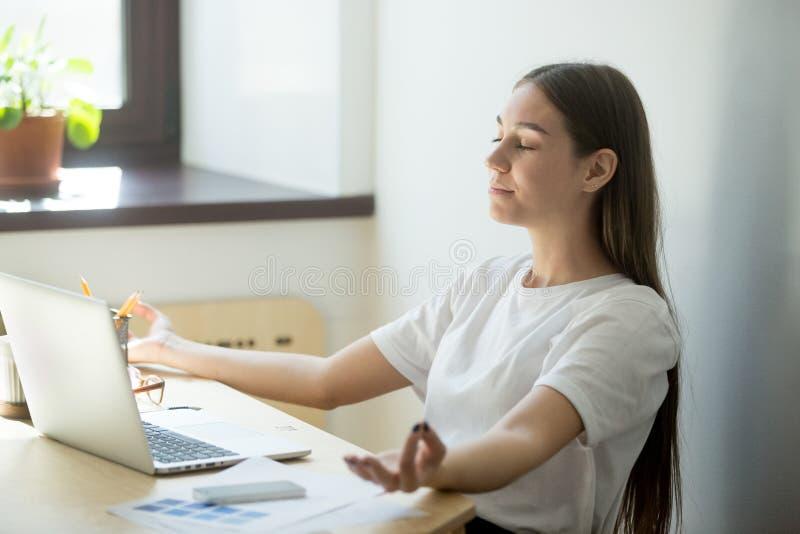 El meditar femenino concentrado en la posición del mudra fotografía de archivo