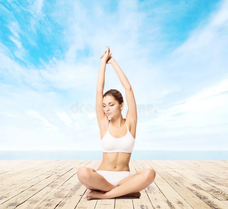 El meditar joven, deportivo, apto y hermoso de la muchacha aislado en whi fotografía de archivo