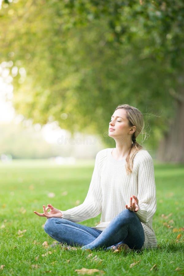 El meditar joven y yoga de la mujer en un parque imágenes de archivo libres de regalías