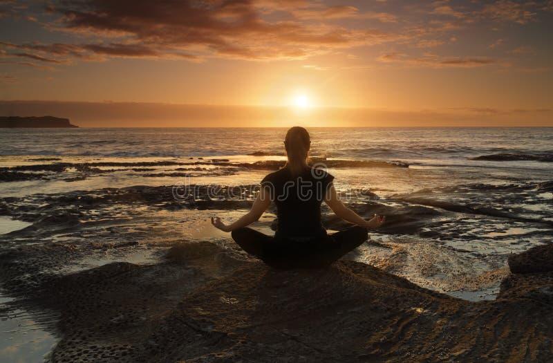 El meditar o yoga por el mar imagen de archivo