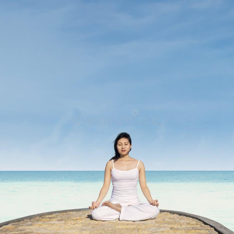 El meditar por la posición de loto en yoga imagen de archivo libre de regalías